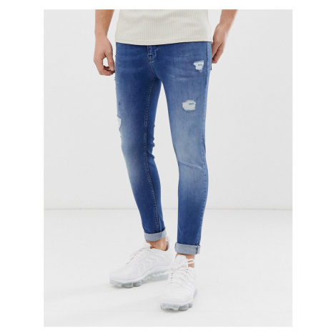 ASOS DESIGN spray on jeans with power stretch in mid wash blue with abrasions