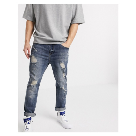 ASOS DESIGN relaxed tapered jeans in dark wash blue with heavy rips