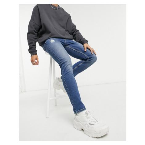 ASOS DESIGN vintage look skinny jeans in dark wash blue with abrasions